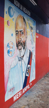 """A mural in memory of its founder, Father Gerard Jean-Juste, now adorns the headquarters of Veye Yo, which means """"Watch them!"""""""