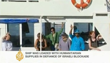 In this video frame, Cynthia McKinney, wearing blue, can be seen waving farewell from the deck of the 'Spirit of Humanity' as the boat sets sail for Gaza on June 29. – Video: Aljazeera