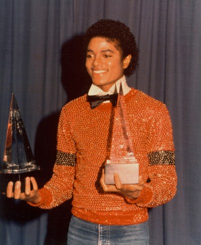 """Michael Jackson accepts the 1981 American Music Award for Favorite Male Vocalist and R&B Album of the Year for """"Off the Wall."""" Having been snubbed at the Grammys that year, he was determined to win the honor. The fact that his talent is now celebrated and he himself cherished around the world predicts his music will never die. And now that his creativity has ceased, perhaps we'll better appreciate the love he showed his people, all people, with lyrics reflecting a high political consciousness and little known but generous support for those doing good in the 'hood, such as YMCAs and Boys and Girls Clubs. – Photo: David Alston's Mahogany Archives"""