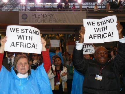 """Chanting and """"signing,"""" """"We stand with Africa!"""" people inside the Bella Center calling for Kyoto targets to be met shut down the climate talks for several hours Monday. – Photo: Nasseem Ackbarally, IPS"""