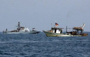 On Aug. 25, 2008, an Israeli gunboat threatens a Palestinian fishing boat riding low in the water with fish desperately needed by starving Gazans. International activists who had arrived that week on the Free Gaza boats that broke the Israeli blockade are on board in hopes their presence will stave off an attack and allow the boat to return home with its catch. – Photo: Reuters