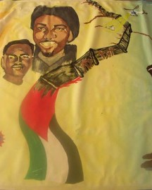 This mural in progress at Poor's new headquarters depicts legally lynched Oscar Grant, legally lynched in Oakland, and the flag and apartheid walls of Palestine, symbols of communities under deadly siege by genocidal forces funded by U.S. taxpayers. – Photo: PNN