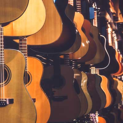 Guitars hanging up in a row in a shop. Representing guitar lessons at SFE Music School