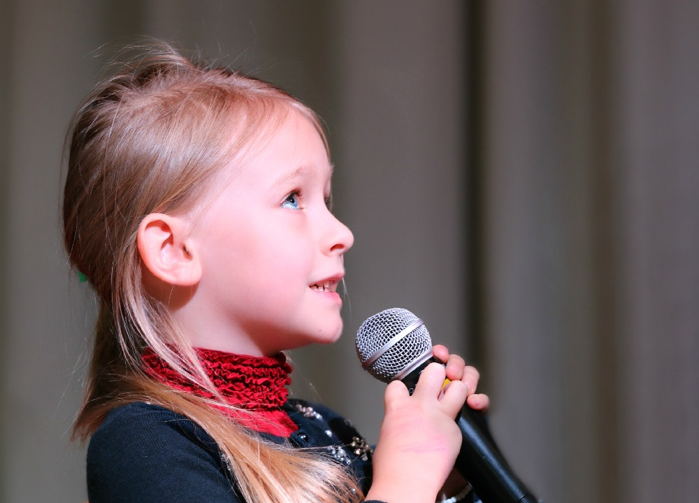 Little girl singing. Representing singing lessons at SFE music school