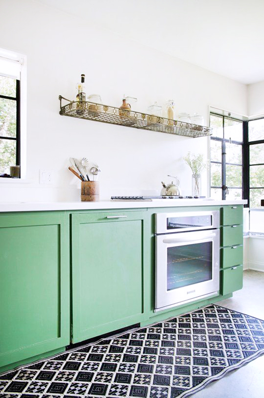 minty green cabinets in modern kitchen with black and white rug / sfgirlbybay