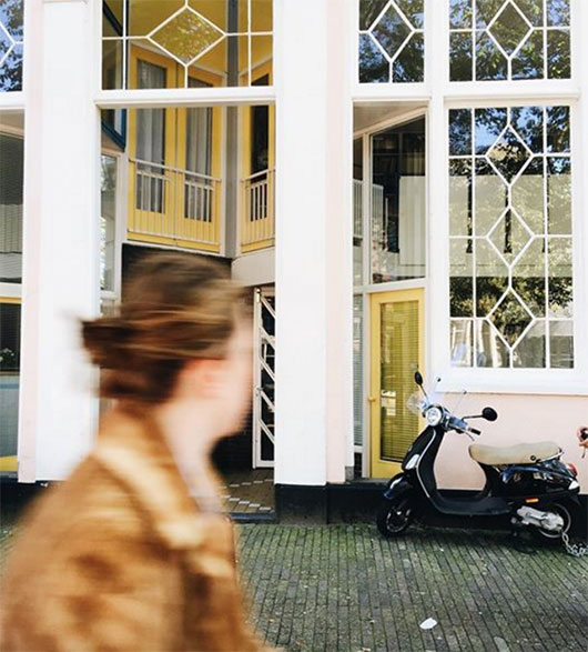 woman in jacket passing a motorbike walking along the Amsterdam canals via @curatedagency. / sfgirlbybay
