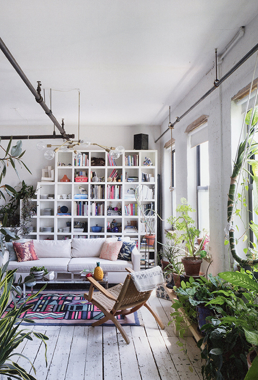 modern living room with exposed pipes, white shelving unit and various houseplants on a bench / sfgirlbybay