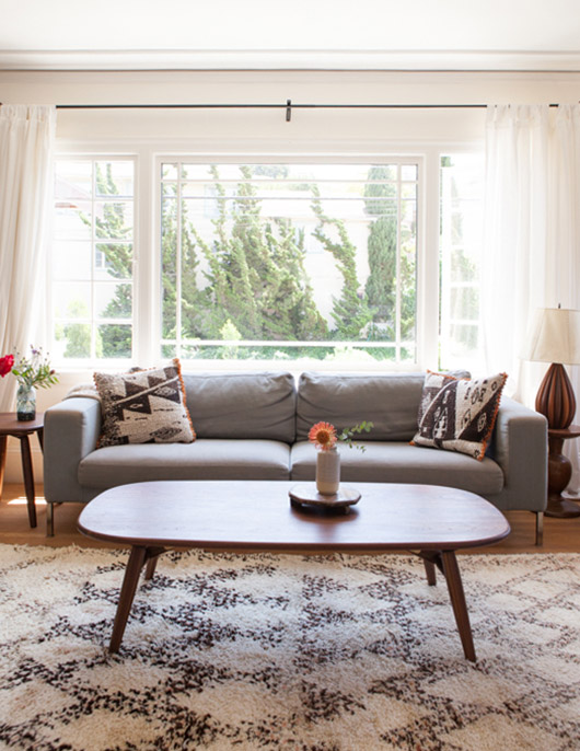 oakland home with a picture window above a gray sofa and handmade coffee table / sfgirlbybay