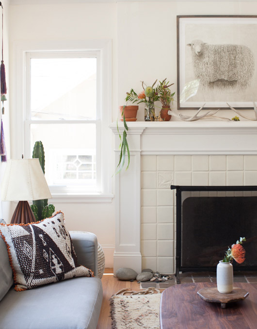 modern home in oakland with white mantle and white tile and black and white framed sheep print above fireplace / sfgirlbybay