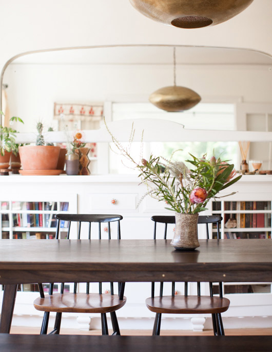 bronze light fixture above dinign table with ceramic pots and plants / sfgirlbybay