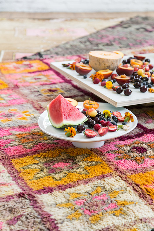 moroccan area rug from abc carpet and home with a white cake stand and fresh cut fruit / sfgirlbybay