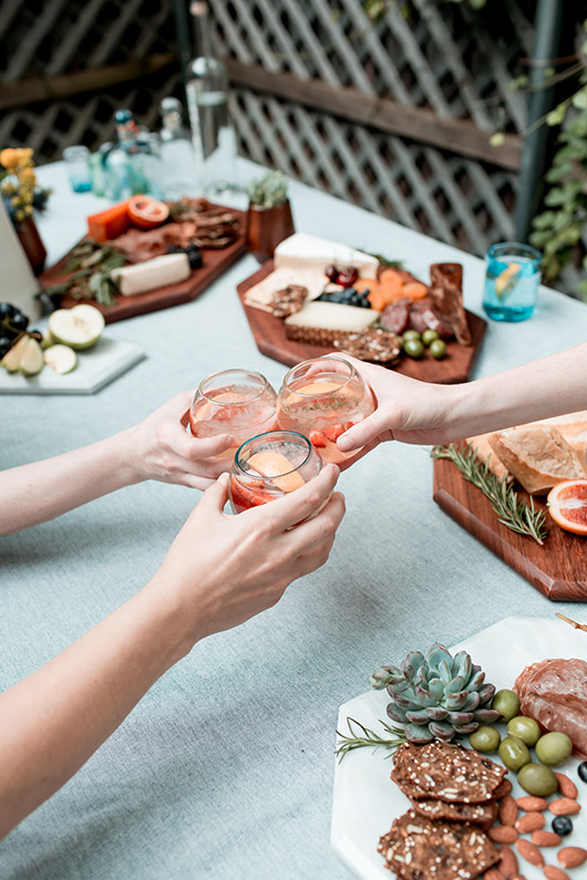 handmade glassware from the citizenry cheersing over outdoor table with serving platters / sfgirlbybay