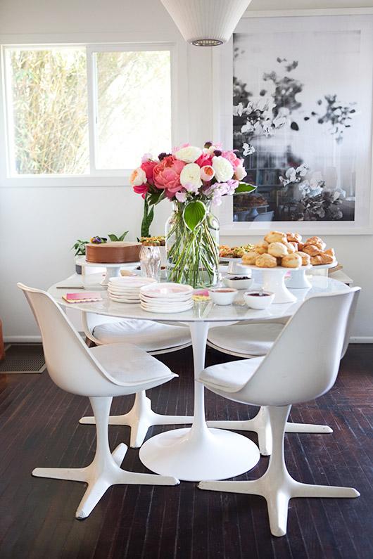 white pedestal table with white tulip chairs and beautiful peonies, roses, sweet peas in a vase delivered fresh from flower muse / sfgirlbybay