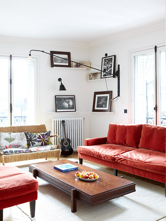 modern white living room with black framed art prints and red velvet sofa photographed by julie ansiau. / sfgirlbybay