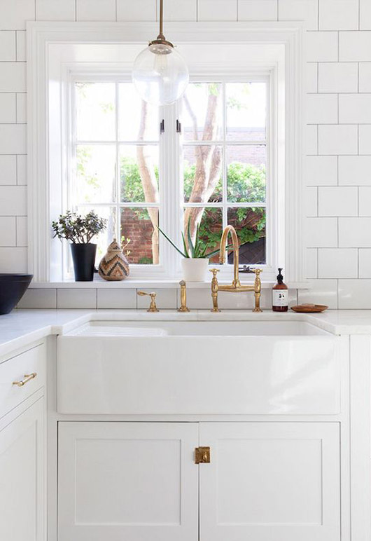 white tiled kitchen with marble countertops and brass fixtures and globe pendant lamp / sfgirlbybay