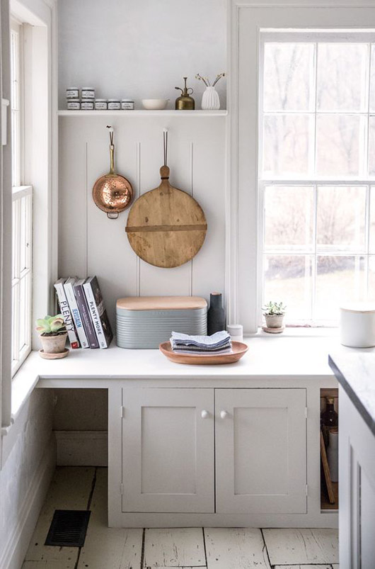 white minimalist kitchen with hanging copper strainer and round wood cutting board and modern bread box and wood serving tray on the counter / sfgirlbybay