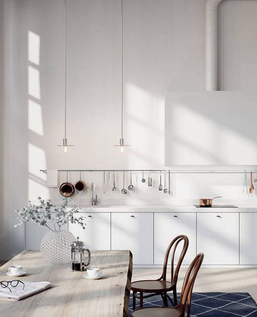 minimalist white kitchen with rustic wood table and navy and white area rug / sfgirlbybay