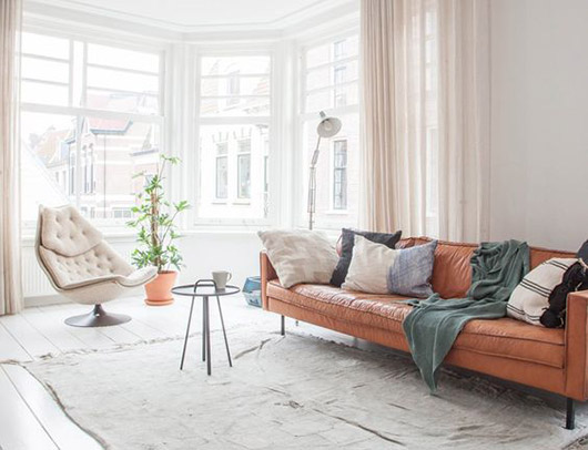 modern decor with orange leather sofa and cream upholstered lounge chair with blue pillows and throw blanket/ sfgirlbybay