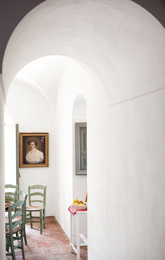 white arched hallway leading to a dining room with green vintage chairs and a gold-framed portrait painting / sfgirlbybay