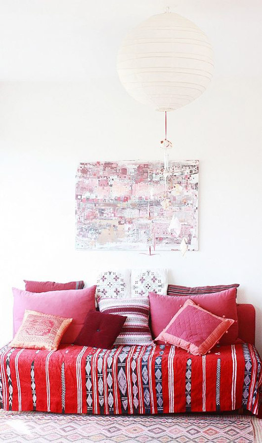 moroccan style throw pillows in shades of red and pink on a sofa covered with a red blanket with black and white geometric patterns / sfgirlbybay