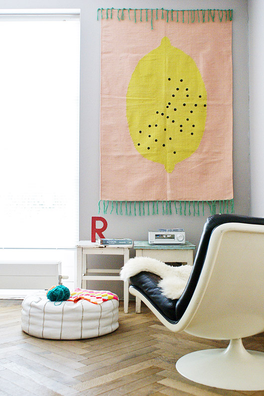 modern room with herringbone wood floors, white leather floor pouf, mid-century modern chair and colorful lemon woven rug hung on the wall / sfgirlbybay