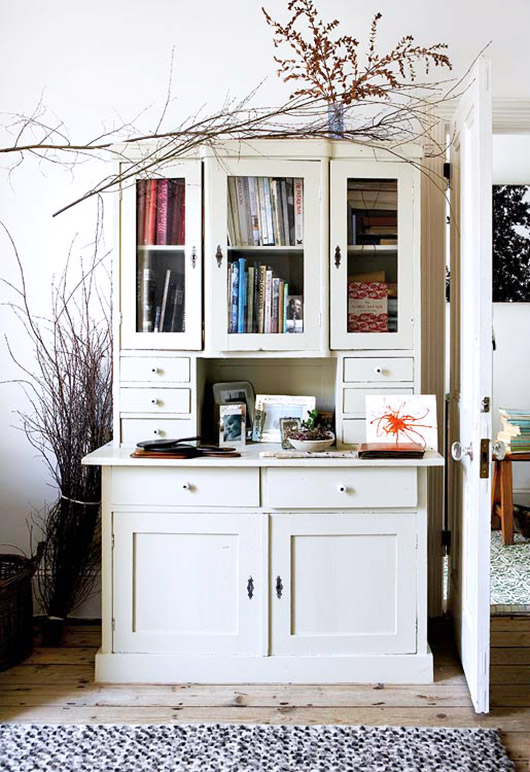 white cabinet decorated with books, vines and branches / sfgirlbybay
