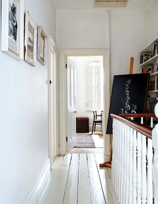 white hallway with railing in victorian meets mid-century modern cottage / sfgirlbybay