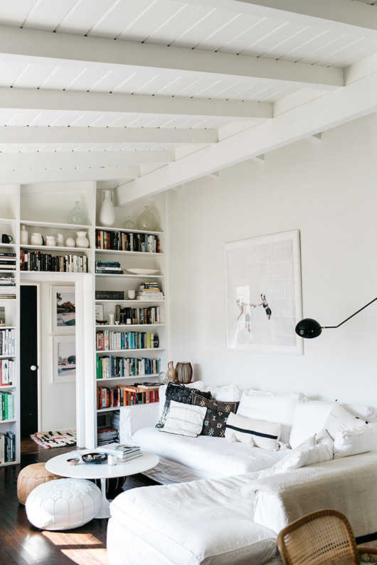 white washed living room with pops of color on bookshelf. / sfgirlbybay
