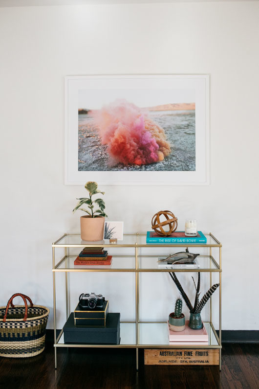 colorful framed photograph over gold table with shelves. / sfgirlbybay