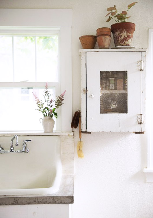 white kitchen with vintage cabinet and potted plants. / sfgirlbybay