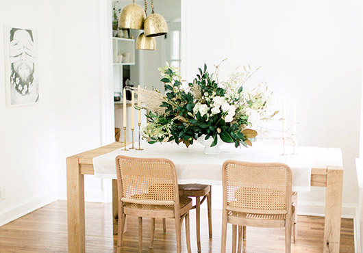 cluster of gold pendant lights over wood dining table with large floral arrangement. / sfgirlbybay