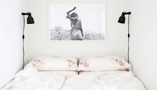black and white photography over bed with two black wall lights. / sfgirlbybay
