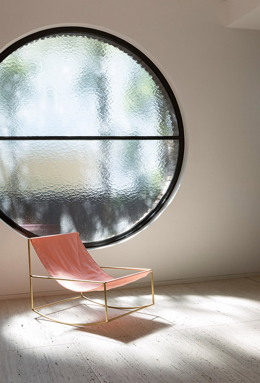 black framed circle window with pink and gold chair. / sfgirlbybay