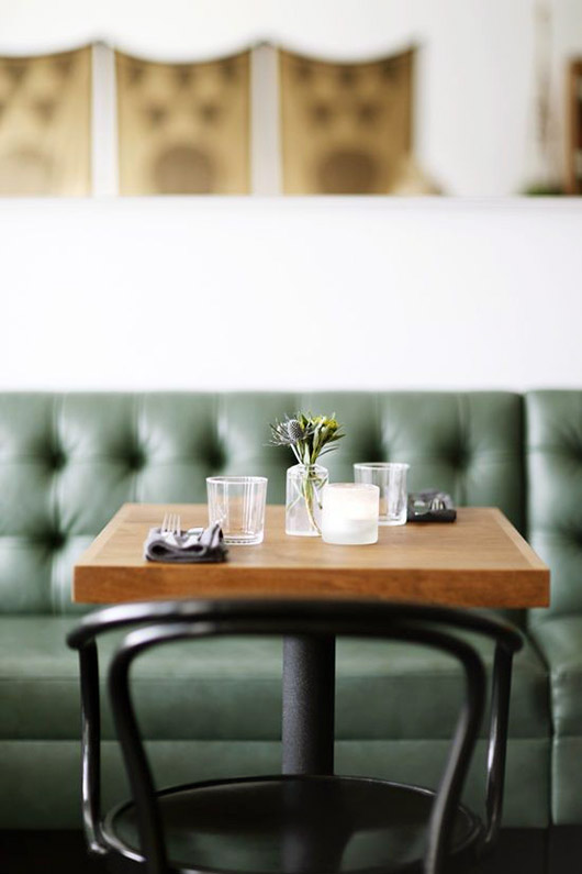 green booth with wood tables and black bentwood dining chairs. / sfgirlbybay