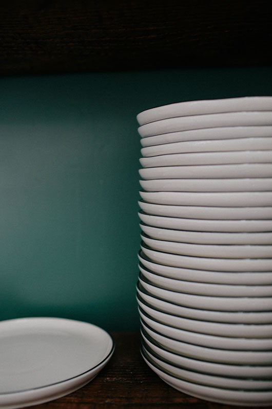 white plates stacked at botanica in los angeles. / sfgirlbybay