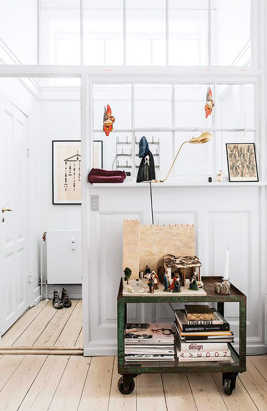 low green rolling cart with book collection and art objects. / sfgirlbybay