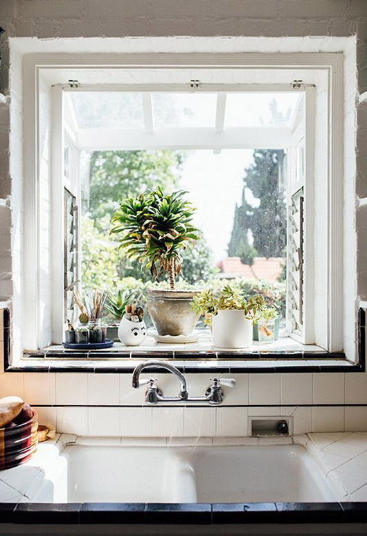 black and white kitchen tile and window above sink with plants. / sfgirlbybay