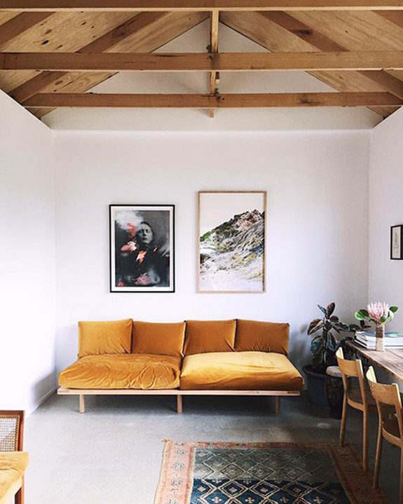 wood beamed ceiling over golden yellow velvet sofa. / sfgirlbybay