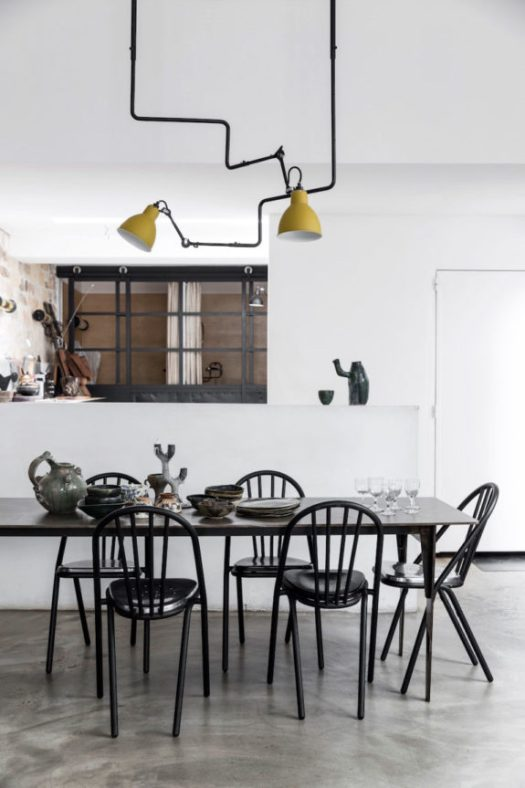 black dining room table and chairs in artist Ema Pradère's ceramic studio in paris. / sfgirlbybay