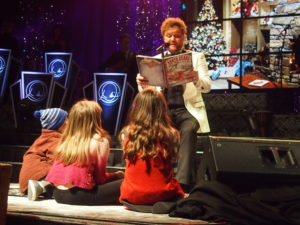"""During his Christmas concert, David Phelps called children from the audience to read his humorous book, """"Santa Claus Get Well Soon."""" Photo by John Herndon"""