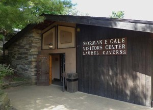 Stone and wood building with a sign reading Norman E Cale Visitors Center Laurel Caverns