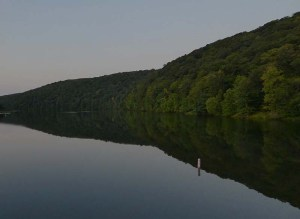 Panorama of wooded hills reflected in still water