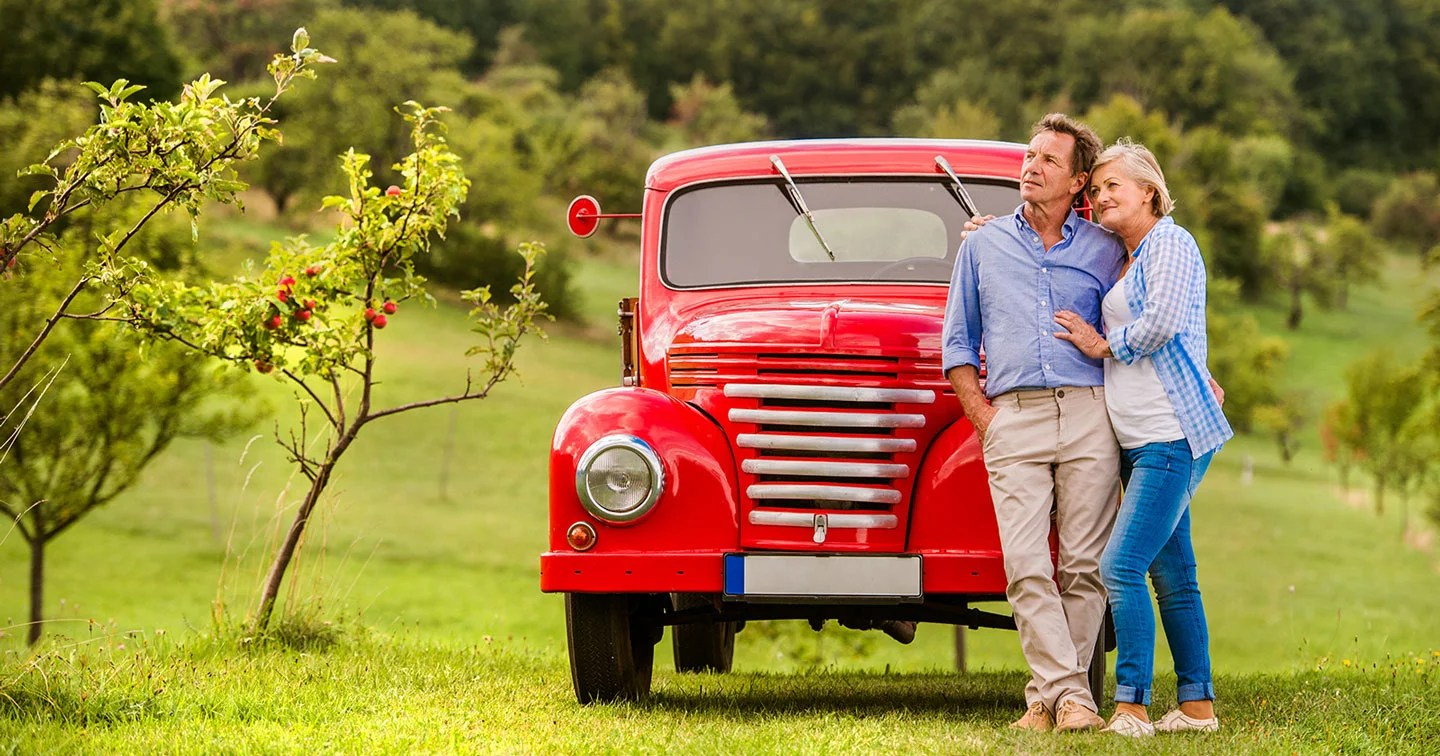 Senior Couple Standing by Red Truck Looking Toward the Future