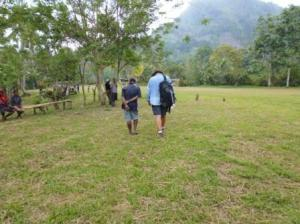 Lim Auwi and Todd Owen talk as they walk to a village meeting.