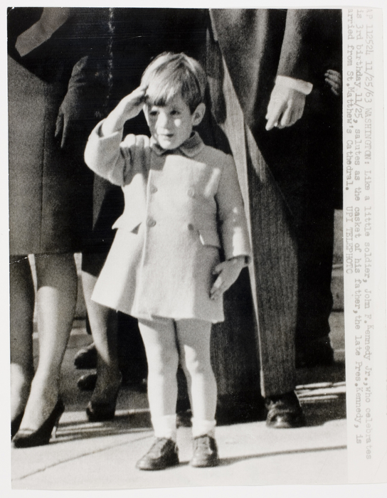 John F. Kennedy giving a salute during his father's funeral