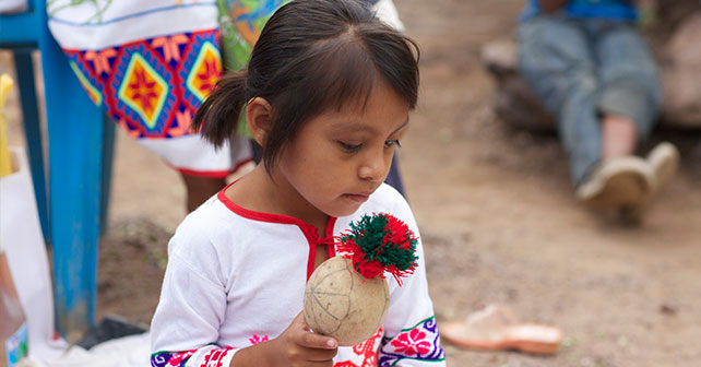 Huichol girl with a ceremonial rattle