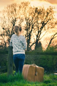 woman suitcase trees fence