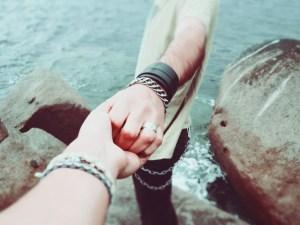hands reaching near river
