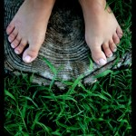 woman's feet on tree stump