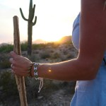 woman hold staff near desert cactus